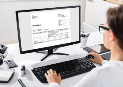 Businesswoman Calculating Invoice On Computer